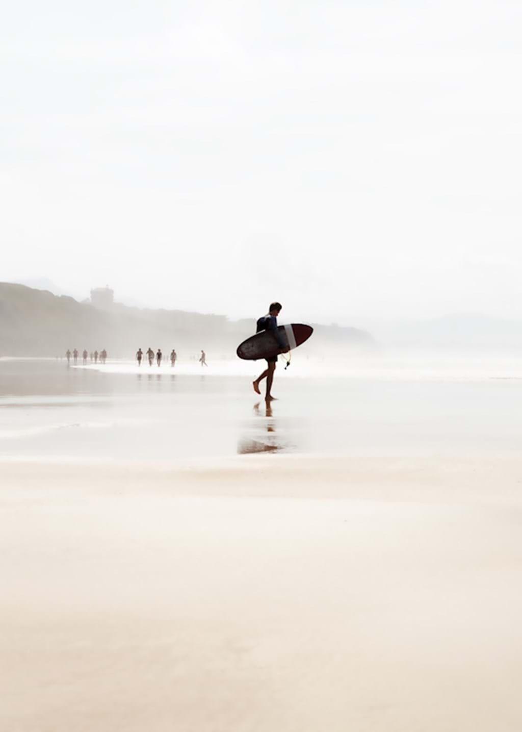Poster: Solo Surfer - A lone person walking out to the ocean with his surfboard under his arm. It...