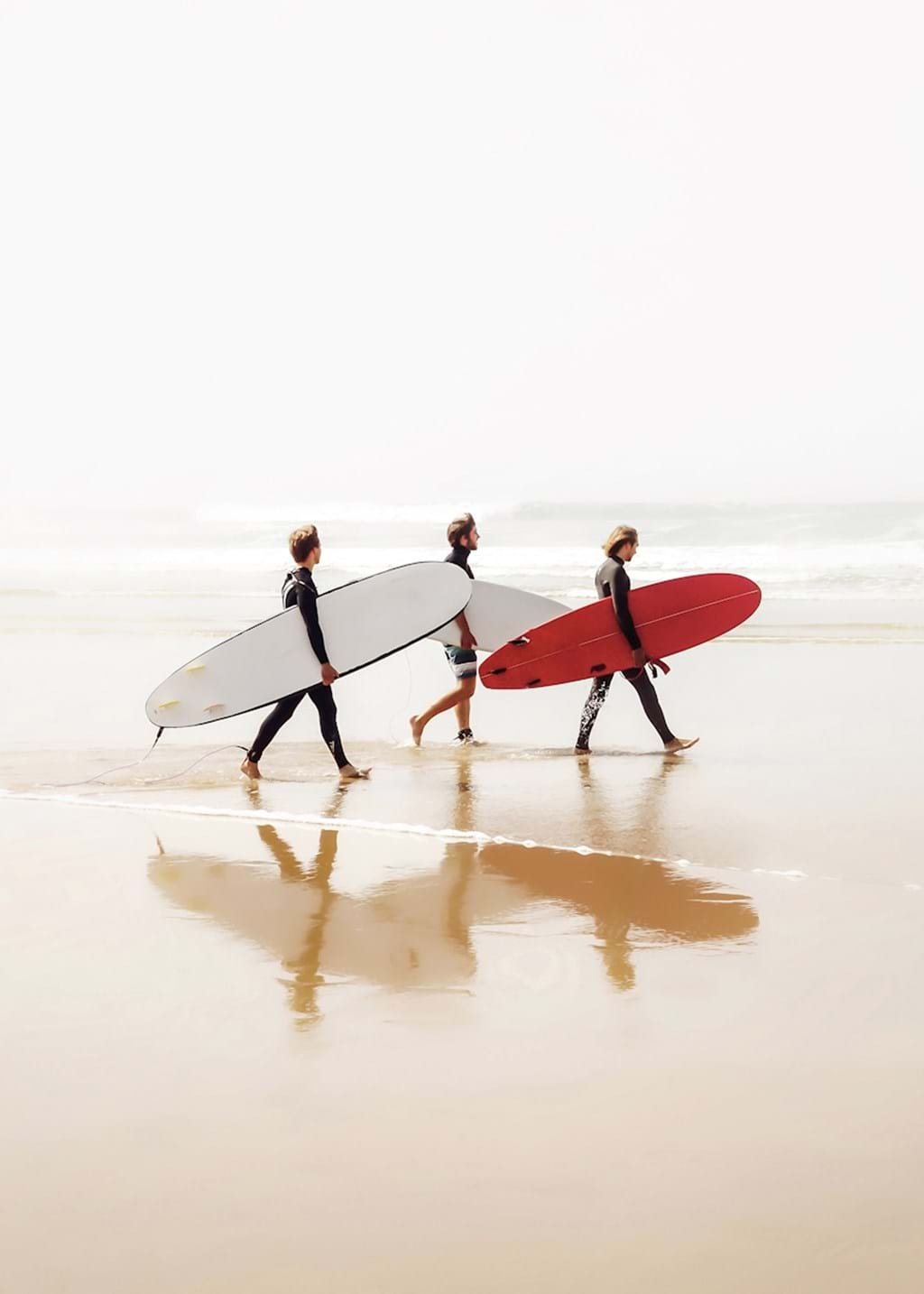 Poster: Triple Surfers - Muted colours and a pop of strong red is in this frame, three surfers walki...